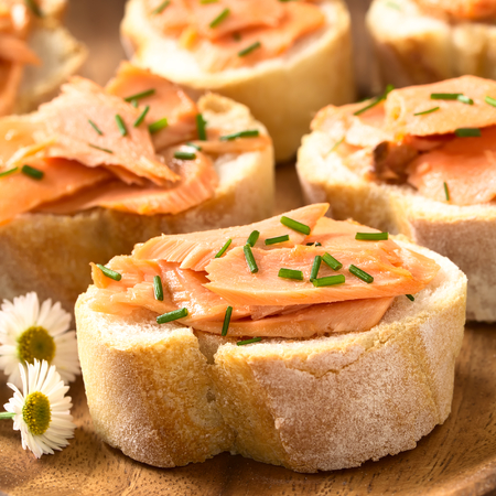 smoked: Smoked salmon sandwiches with chives, photographed with natural light (Selective Focus, Focus on the front of the salmon on the first bread)