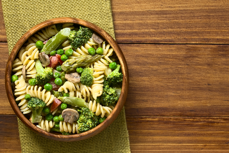 Pasta primavera with green asparagus, pea, broccoli, mushroom and tomato in cream sauce served in wooden bowl, photographed overhead on dark wood with natural light