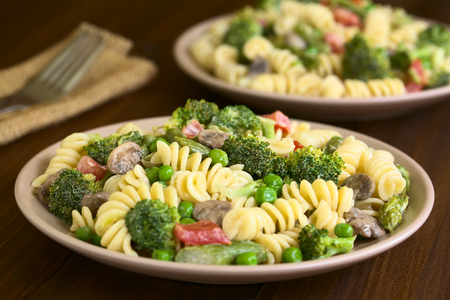 primavera: Pasta primavera with green asparagus, pea, broccoli, mushroom and tomato in cream sauce served on plates, photographed on dark wood with natural light (Selective Focus, Focus in the middle of the pasta on the first plate)