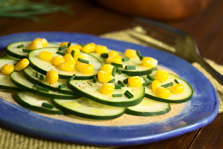 accompaniment: Fresh cucumber and corn salad with chives served on plate, photographed with natural light (Selective Focus, Focus in the middle of the salad) Stock Photo