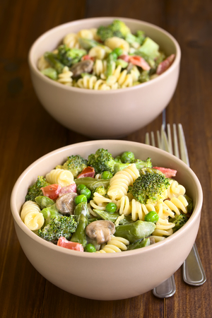 primavera: Pasta primavera with green asparagus, pea, broccoli, mushroom and tomato in cream sauce served in two bowls, photographed on dark wood with natural light (Selective Focus, Focus in the middle of the first bowl)