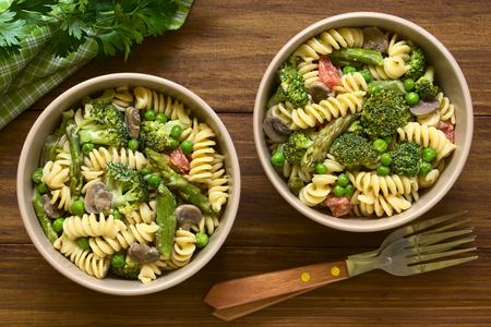 primavera: Pasta primavera with green asparagus, pea, broccoli, mushroom and tomato in cream sauce served in bowls, photographed overhead on dark wood with natural light