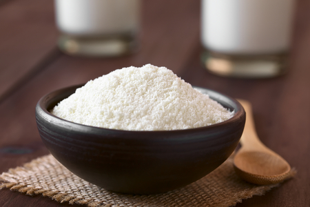 Powdered or dried milk in small bowl, photographed on dark wood with natural light (Selective Focus, Focus one third into the milk powder) Stockfoto