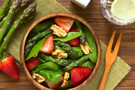 baby spinach: Fresh strawberry, green asparagus, baby spinach and walnut salad served in wooden bowl, photographed overhead on dark wood with natural light (Selective Focus, Focus on the top of the salad) Stock Photo