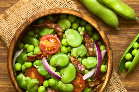 broad: Broad bean, green pea, cherry tomato, red onion and fried bacon salad in wooden bowl, photographed overhead on dark wood with natural light