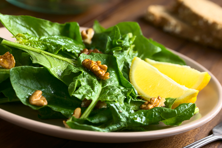 side plate: Fresh spinach and walnut salad with lemon wedges on the side served on plate, photographed with natural light (Selective Focus, Focus on the walnut in the middle of the image and the one in front of the lemon)