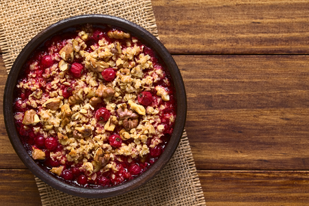 redcurrant: Redcurrant crumble or crisp with oatmeal and walnut on top baked in rustic bowl, photographed overhead on dark wood with natural light (Selective Focus, Focus on the top of the crumble)