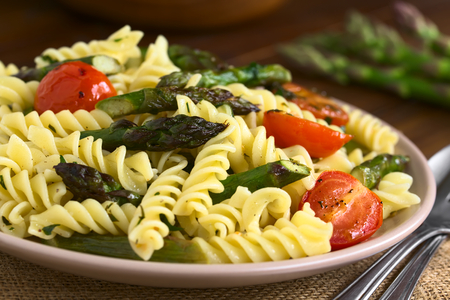 Baked green asparagus, cherry tomato and rotini pasta salad served on plate, photographed on dark wood with natural light (Selective Focus, Focus on the asparagus head in the middle of the image)