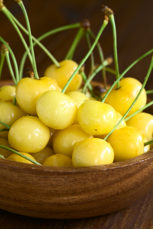 natural light: Ripe yellow or Rainier cherry in wooden bowl, photographed with natural light (Selective Focus, Focus one third into the cherries) Stock Photo