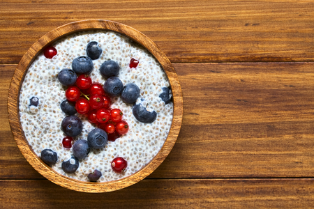 hispanica: Chia (lat. Salvia hispanica) seed pudding with blueberries and redcurrants in wooden bowl, photographed overhead on wood with natural light (Selective Focus, Focus on the top of the pudding)