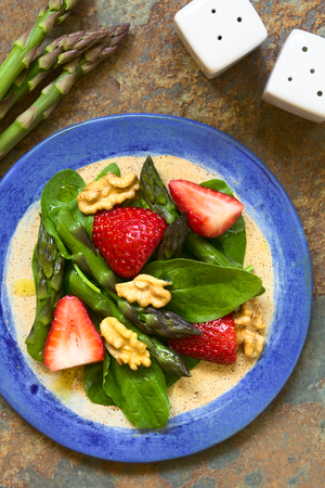 baby spinach: Fresh strawberry, green asparagus, baby spinach and walnut salad served on plate, photographed overhead on slate with natural light