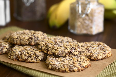 oatmeal cookie: Vegan cookies made of banana, oatmeal and roasted oat grains, linseed, poppy seeds, grated coconut, chia seeds and cinnamon powder, photographed with natural light (Selective Focus, Focus on the front of the top cookie)