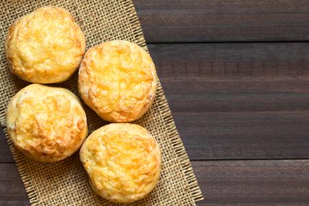 bollos: Húngaro queso tradicional pogácsa salados al horno pastelería similar al pan, fotografiado por encima en madera oscura con luz natural (enfoque selectivo, centrarse en la parte superior de los pasteles)