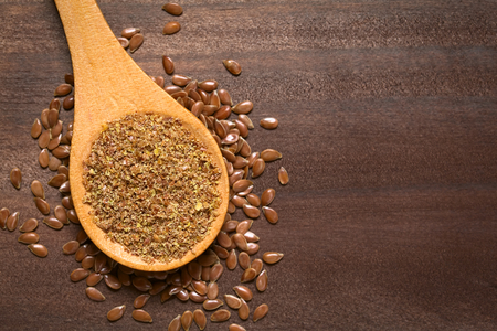 flaxseed: Ground or crushed brown flax seed or linseed on wooden spoon, photographed on dark wood with natural light
