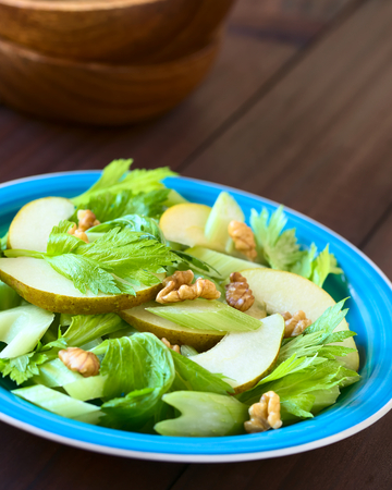 Fresh celery, pear and walnut salad on blue plate, photographed with natural light (Selective Focus, Focus in the middle of the salad)