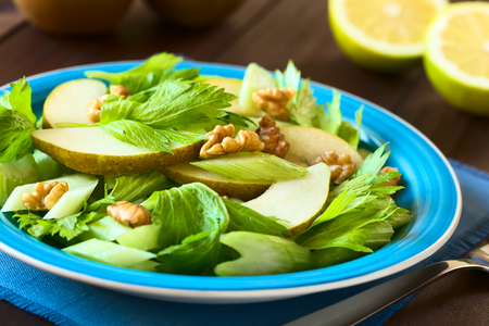 Fresh celery, pear and walnut salad on blue plate, with half lemons in the back, photographed with natural light (Selective Focus, Focus in the middle of the image) Stock Photo