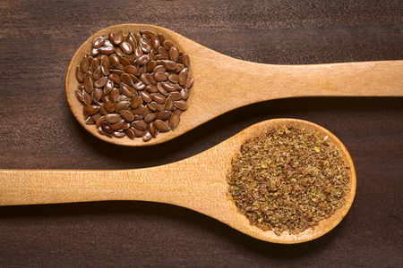 brown flax: Whole and ground  brown flax seeds or linseeds on wooden spoons, photographed on dark wood with natural light Stock Photo