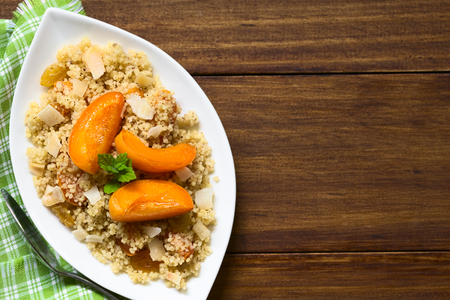 lemon balm: Couscous dessert with apricots, yellow raisins, coconut flakes and cinnamon served on plate and garnished with lemon balm leaf, photographed overhead with natural light (Selective Focus, Focus on the top of the dessert)
