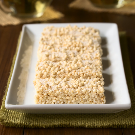 quadratic: Baked marshmallow, popped quinoa and coconut bars on white plate, photographed with natural light (Selective Focus, Focus on the front of the first bar)