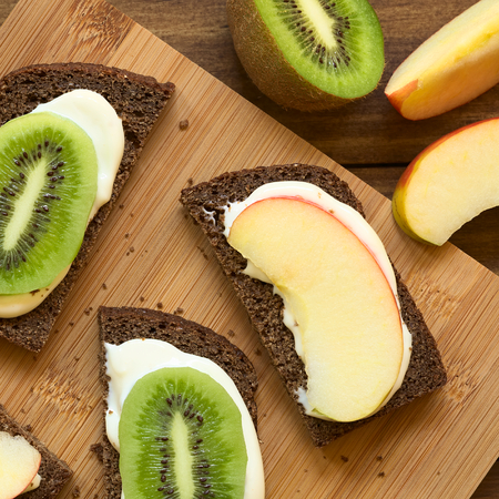 quadratic: Wholegrain bread sandwiches with cream cheese and fresh apple or kiwi slices, photographed overhead with natural light Stock Photo