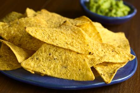 tortilla de maiz: chips de tortilla de maíz con salsa de aguacate en la parte posterior, fotografiada con luz natural (enfoque selectivo, enfoque en el borde delantero de la tortilla chip en el centro de la imagen) Foto de archivo