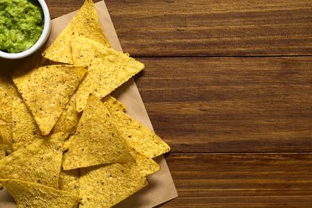 tortilla de maiz: chips de tortilla de maíz con salsa de aguacate, fotografiados por encima de la madera con luz natural