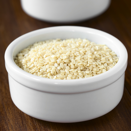 quadratic: White sesame seeds in small bowl, photographed with natural light (Selective Focus, Focus one third into the seeds)