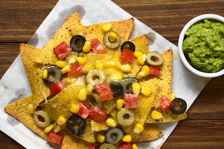 corn meal: Baked nachos with cheese, green and black olives, tomato and corn, with guacamole on the side, photographed overhead with natural light (Selective Focus, Focus on the top of the meal)