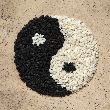 complement: Black and white sesame seeds forming the yin and yang symbol, photographed overhead with natural light Stock Photo
