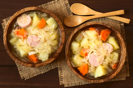 potato soup: Sauerkraut soup or stew prepared with potato, carrot and bratwurst served in wooden bowls, photographed overhead on dark wood with natural light Stock Photo