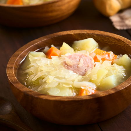 prepared dish: Sauerkraut soup or stew prepared with potato, carrot and bratwurst served in wooden bowl, photographed with natural light (Selective Focus, Focus in the middle of the dish) Stock Photo
