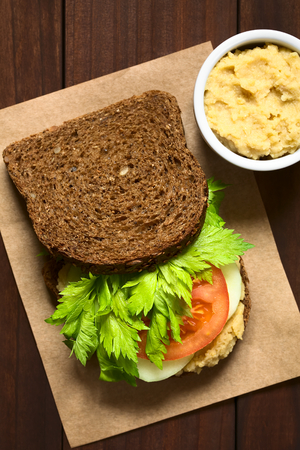 PULSE: Vegan wholegrain sandwich with celery leaves, tomato, cucumber and chickpea spread or hummus, photographed overhead with natural light (Selective Focus, Focus on the celery and tomato, and the hummus in the bowl)