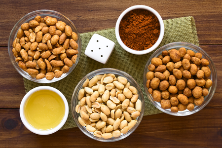 coated: Peanut snacks in glass bowls. Peanuts with honey and salt, salted peanuts, peanuts roasted in a spicy coat. Photographed overhead on dark wood with natural light.