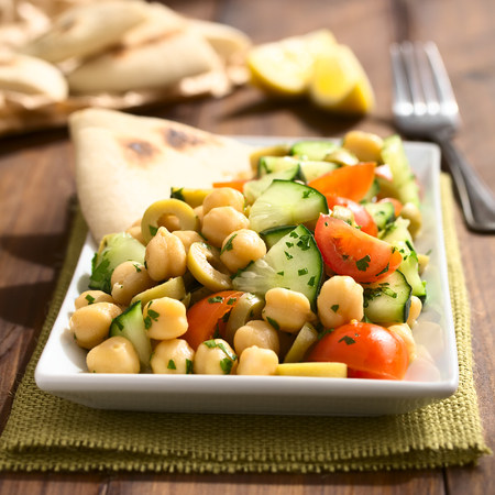 Chickpea salad with green olives, cucumber, cherry tomato and parsley, served on plate with pita bread pieces in the back, photographed with natural light (Selective Focus, Focus one third into the salad)