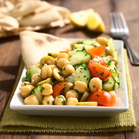 Kikkererwtensalade met groene olijven, komkommer, kersentomaat en peterselie, geserveerd op de plaat met stukjes pitabroodje achteraan, gefotografeerd met natuurlijk licht (selectieve focus, focus eenderde in de salade)