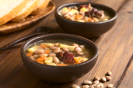 pinto bean: Traditional Hungarian Babgulyas (bean goulash), a soup made of pinto beans, smoked meat, potato, carrot, csipetke (homemade soup pasta), served in rustic bowls, photographed with natural light (Selective Focus, Focus on the meat) Stock Photo