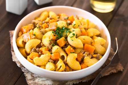 mincemeat: Macaroni pasta with creamy pumpkin and mincemeat sauce garnished with parsley served in white bowl, photographed with natural light (Selective Focus, Focus in the middle of the dish)