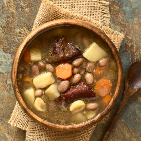 pinto bean: Traditional Hungarian Babgulyas (bean goulash), a soup made of pinto beans, smoked meat, potato, carrot, csipetke (homemade soup pasta), garlic, onion, served in wooden bowl, photographed overhead on slate with natural light