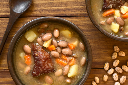 pinto bean: Traditional Hungarian Babgulyas (bean goulash), a soup made of pinto beans, smoked meat, potato, carrot, csipetke (homemade soup pasta), garlic, onion, served in rustic bowls, photographed overhead with natural light
