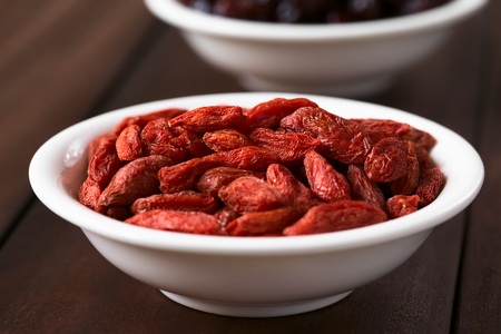 chinese wolfberry: Dried gojis or wolfberries in small bowl, photographed with natural light (Selective Focus, Focus on the top berries)