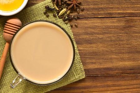 Homemade Indian Masala Chai Tea made of black tea, a variety of spices and mixed with milk, honey and ingredients on the side, photographed overhead on dark wood with natural light (Selective Focus, Focus on the top of the tea)