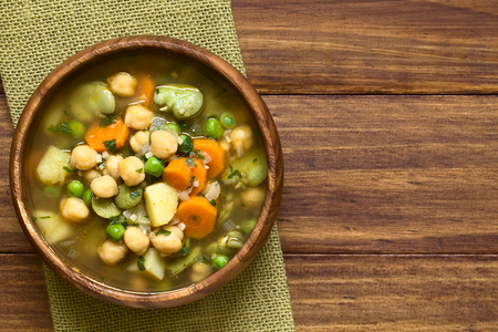 fava bean: Vegetarian chickpea soup with carrot, broad bean (fava bean), pea, potato, onion, garlic and parsley served in wooden bowl, photographed overhead on wood with natural light