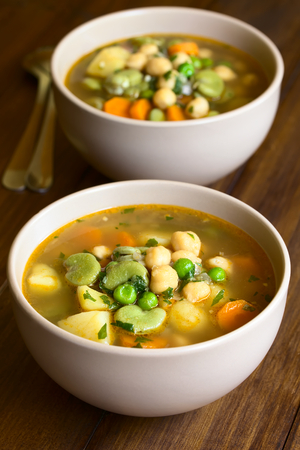 fava bean: Vegetarian chickpea soup with carrot, broad bean (fava bean), pea, potato, onion, garlic and parsley served in bowl, photographed on wood with natural light (Selective Focus, Focus in the middle of the first soup) Stock Photo
