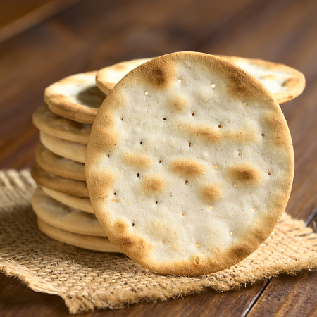 light circular: Saltine or soda crackers, photographed on dark wood with natural ight (Selective Focus, Focus on the standing cracker) Stock Photo