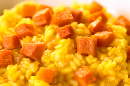 Pumpkin risotto prepared with pumpkin puree, roasted pumpkin pieces on top, photographed with natural light (Selective Focus, Focus one third into the risotto)