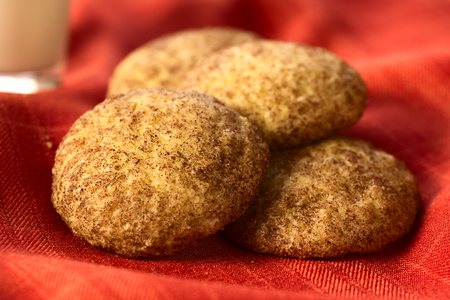 sugar cookie: Homemade snickerdoodle cookies with cinnamon and sugar coating on red fabric, photographed with natural light (Selective Focus, Focus in the middle of the left cookie and the front edge of the right one)
