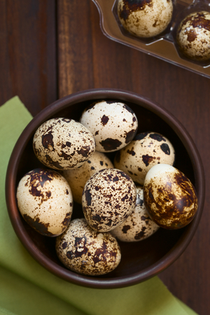 Fresh raw quail eggs in rustic bowl, photographed overhead with natural light (Selective Focus, Focus on the top of the eggs on the top)