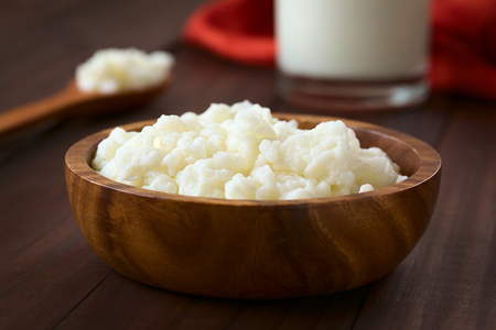 Milk kefir grains in wooden bowl with a glass of kefir in the back, photographed with natural light (Selective Focus, Focus one third into the kefir grains)