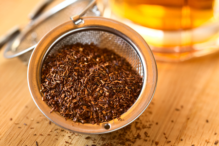 Rooibos herbal tea in strainer with freshly prepared tea in the back, photographed with natural light (Selective Focus, Focus one third into the leaves) Standard-Bild
