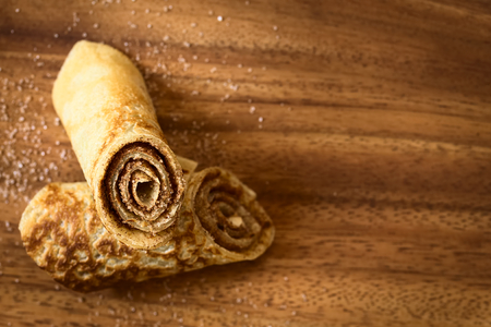 filled roll: Crepe rolls filled with cinnamon and sugar, photographed overhead on wood with natural light (Selective Focus, Focus on the front of the upper roll)